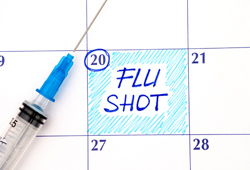 calendar marking date to get flu shot with epidermic needle laid on top