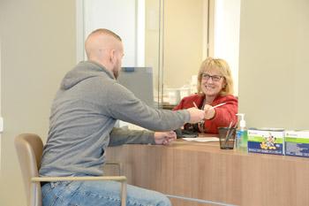 woman sitting behind office desk handing young man paperwork