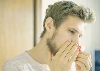 young man pinching nose bleed